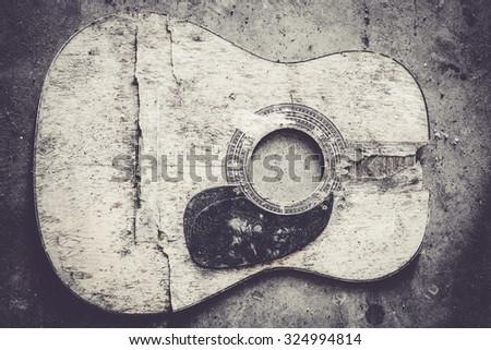 Broken guitar on messy concrete floor - stock photo