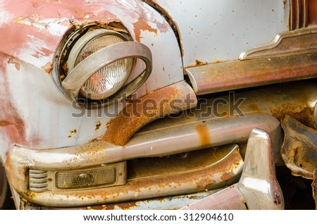 Broken headlamp on abandoned vintage car  - stock photo