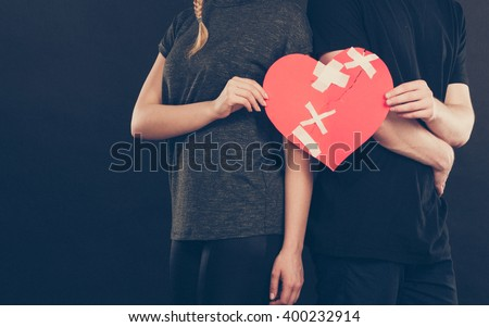 Broken heart difficult love concept. Couple woman and man hands holding paper red heart fixed with plaster bandage. Rift in relations. - stock photo