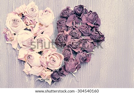 Broken heart of dried roses on wooden background - stock photo