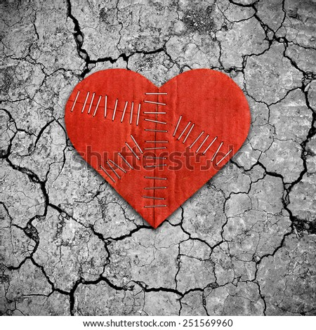 Broken heart on dry cracked soil - stock photo