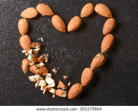 Broken heart shape made with almonds - stock photo