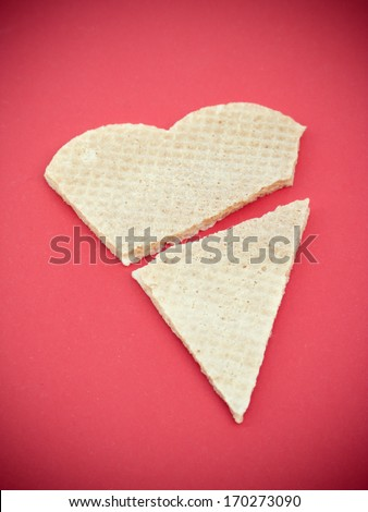 Broken heart shaped biscuit on red background - stock photo