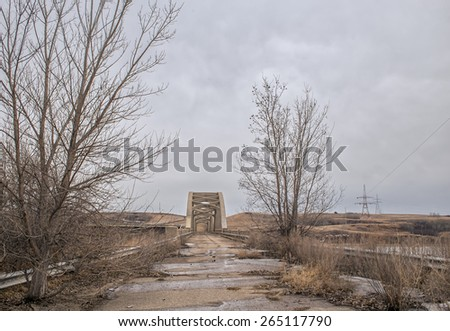 Broken highway and two bare trees leading up to an old abandoned concrete bridge - stock photo