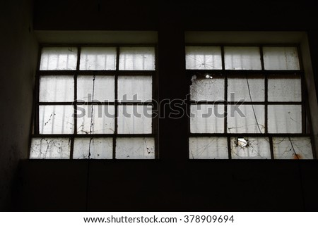Broken industrial windows in dark abandoned factory interior.