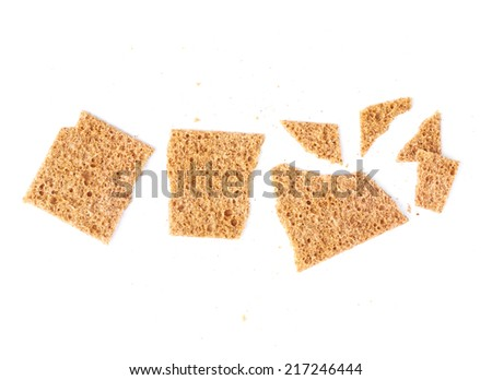 Broken into pieces and crumbs single bread cracker snack isolated over the white background - stock photo
