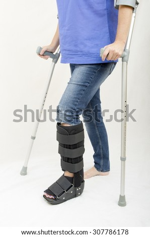 Broken Leg and Crutches and Support A lady with a fractured leg in an orthopaedic boot walking with the aid of crutches - stock photo