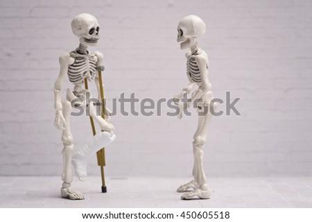 Broken leg skeleton chatting with his friend - stock photo
