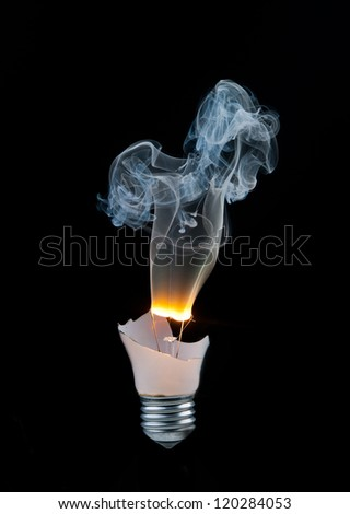 Broken light bulb burns and smoke from it on a black background