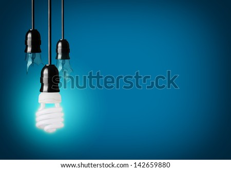 broken light bulbs and energy saver bulb on blue background - stock photo