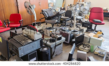 Broken office chairs and electronic waste in the store room - stock photo