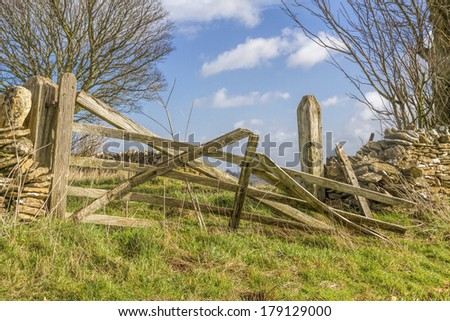Broken old farm gate with drystone wall, in the Cotswolds,Gloucester, England - stock photo