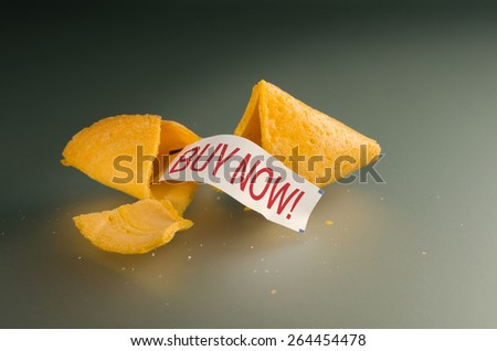 Broken open fortune cookie with a fortune message of BUY NOW! representing business finance, stock market, financial strategies and marketing success, and much more. - stock photo