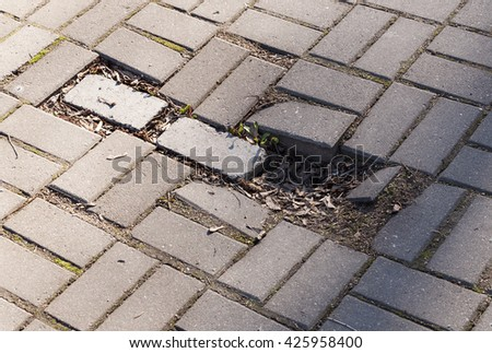 Broken pavement without some stones. Dangerous roadway for a pedestrians. - stock photo