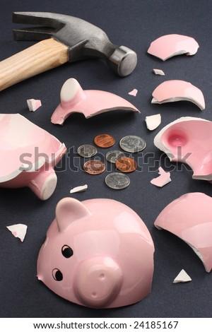 Broken piggy bank containing few coins conveying a sense of misery and financial despair. - stock photo