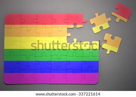 broken puzzle with the gay flag  on a gray background - stock photo