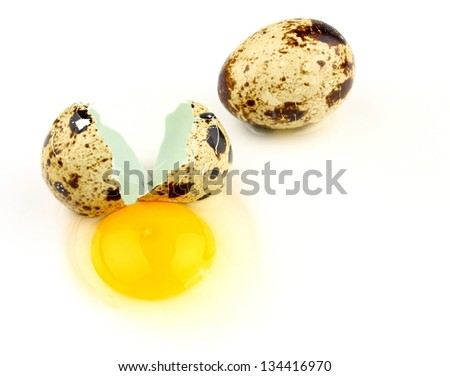 Broken quail egg on white background, top view