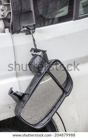 broken rear-view mirror hanging, reflecting the asphalt - stock photo