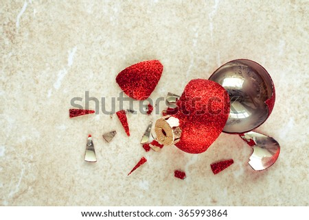 broken red Christmas ball on the stone floor - stock photo