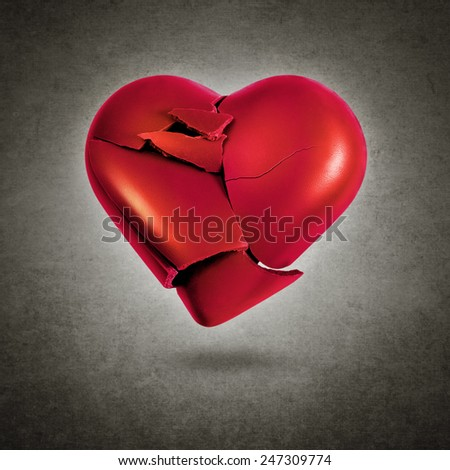 Broken red heart hovering over a gray textured background - stock photo