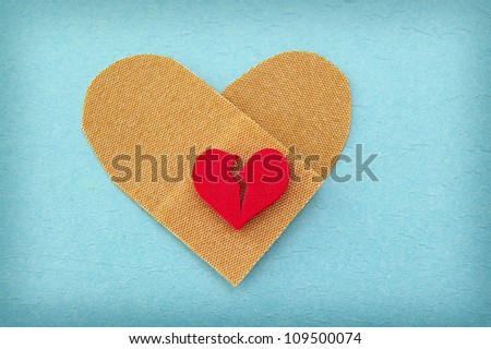 broken red heart on a heart shaped bandage - stock photo