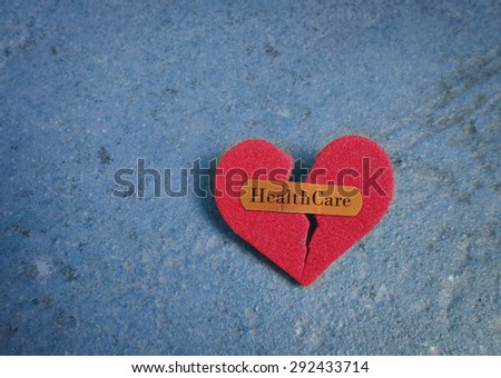Broken red heart with a bandaid and Healthcare text, on blue                                - stock photo