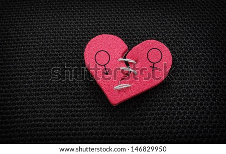 broken red heart with threaded stitches, and male - female symbols - stock photo