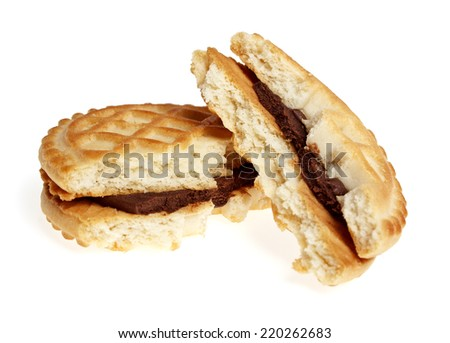 Broken sandwich biscuits with chocolate cream on a white background