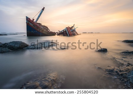 Broken ship with the sunset sky - stock photo