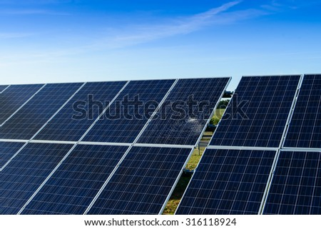 broken solar panel among whole panels against a blue sky