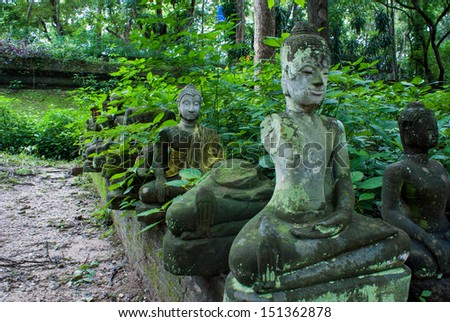 "Broken statues of Buddha in a forest temple """"Wat U-Mong"" Chiangmai, Thailand"