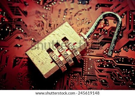 broken unlock security lock on computer circuit board - computer security breach concept - stock photo