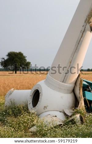 broken wind turbines on green field. Alternative source of energy - stock photo