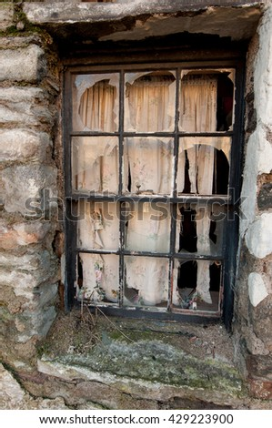 Broken window of a derelect cottage in the Scottish highland village of Kenmore.