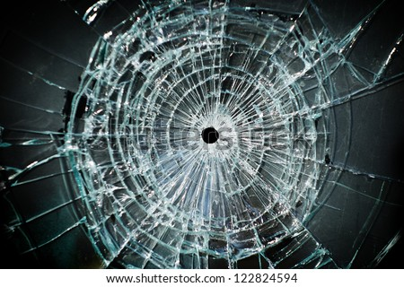 Broken window with a bullet hole in the middle - stock photo
