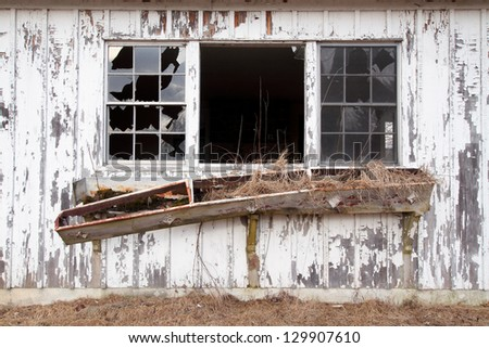 Broken windows and window box of an old abandoned farmhouse in the Delaware Water Gap National Recreation Area - stock photo