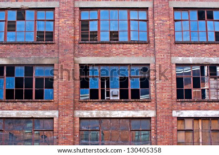 Broken windows on old derelict building with reflections - stock photo