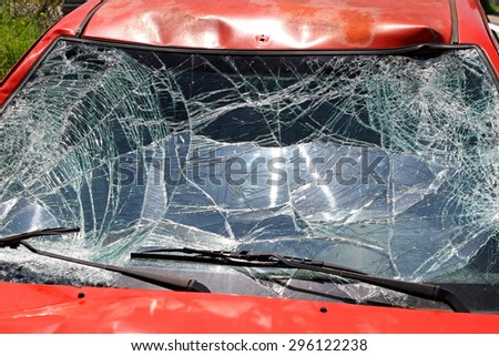 Broken Windshield at Red Car in Traffic Accident - stock photo