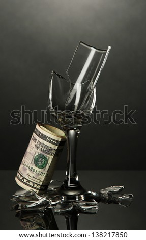 Broken wineglass and money on grey background