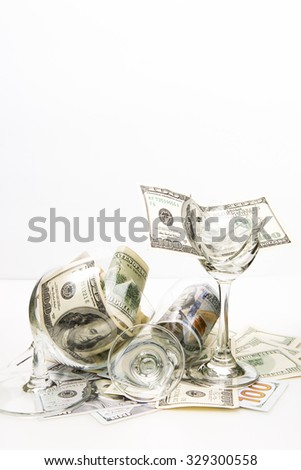 Broken wineglass and money on white background