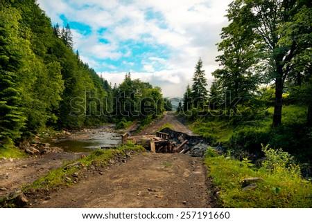 Broken wooden bridge on the mountain river in the Carpathians, Ukraine - stock photo