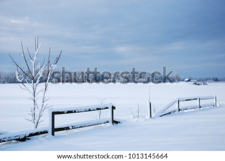 Broken wooden fence in a wintry landscape