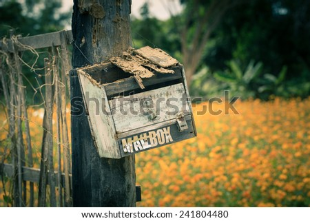 Broken wooden mail box in the garden - stock photo