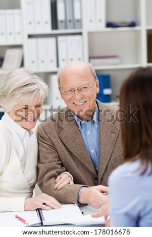 Broker chatting to a smiling senior couple as they sit at the desk in her office discussing finances or insurance - stock photo