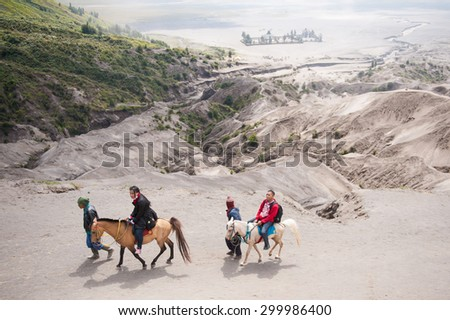 BROMO, INDONESIA - JULY 21, 2013 : Indonesians provide horse rental for tourists from parking area to trekking starting point on 21 july 2013 at Mount Bromo in Java , Indonesia.  - stock photo