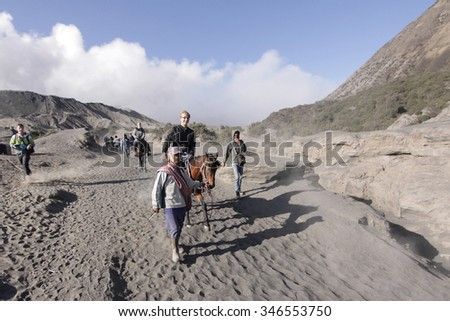 BROMO, INDONESIA - NOVEMBER 17: A ltourist riding a horse to came down from Bromo crater. Horse riding can be rent from below of the mountain to get to the crater of Mount Bromo 17 November 2015 - stock photo