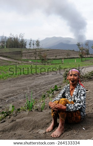 BROMO, JAVA, INDONESIA - MARCH 26: Ethnic woman living in the area of the Bromo volcano is sitting on the volcanic ash with the tobacco in the mouth during the eruption of the Bromo on March 26, 2011. - stock photo