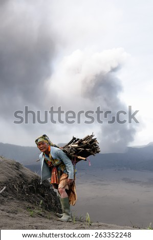 BROMO, JAVA, INDONESIA - MARCH 26: The ethnic woman living  in the area of the Bromo volcano is carrying firewood in of crater in the course of the eruption of the Bromo on March 26, 2011. - stock photo