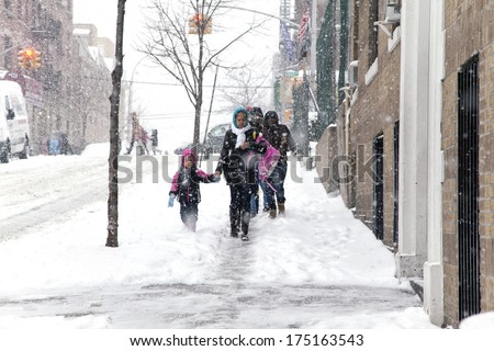 BRONX, NEW YORK - JANUARY 21: A small child and mother weathering a 6 to 10 inch snow storm and teen temperatures along Ogden avenue and 162nd street.  Taken January  21,  2014  the Bronx,  New York.