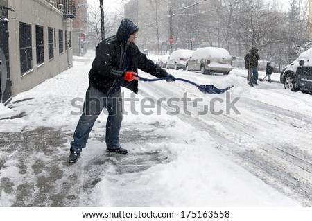 BRONX, NEW YORK - JANUARY 21: man shoveling during  a 6 to 10 inch snow storm and teen temperatures along Ogden avenue and 162nd street.  Taken January  21,  2014 in the Bronx,  New York. - stock photo